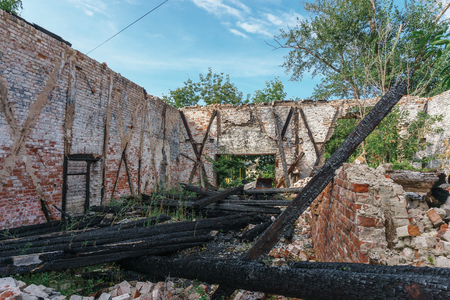 abandoned warehouse: abandoned Warehouse with a crumbling roof and charred wooden logs in Samara