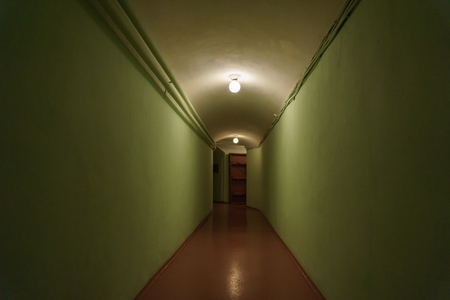 dark corridor with green walls and a light bulb on the ceiling