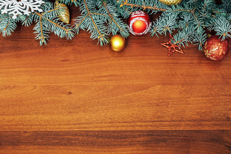 christma: Christmas tree branches with Christmas toys on wooden background. Space for text Stock Photo