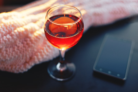 Red wine and mobile phone with white blanket.Sunny evening.Toned bokeh image.