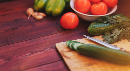 kitchen workplace concept. fresh vegetables, cutting board and knife on wooden table background Stock Photo