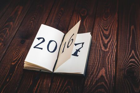 New year concept for 2017 opened notepad on wooden rustic background, written 2016, 2017 can be seen on the next page. Cope space