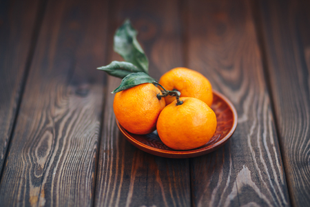 tangerines on wooden plate with leaves on wooden background closeup. organic vegetarian diet concept. winter mandarin. copy space Stock Photo