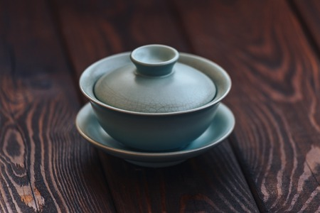 Gaiwan or tea cup for Chinese tea ceremony on wooden background. Copy space.