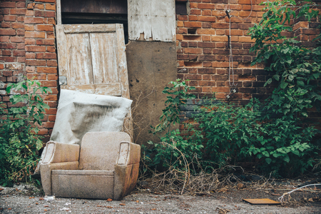 cast in place: old chair on the brick wall background. cast housing. deserted place, abandoned by people