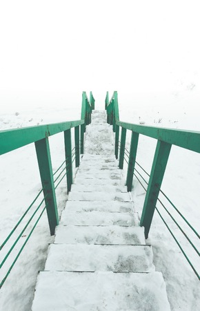 nowhere: Stairs to nowhere concept. green railings and steps in snow. View to white space. Vertical picture. Stock Photo