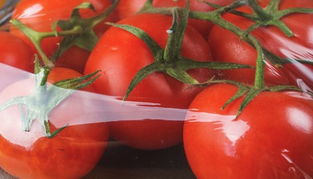 Ripe raw red tomatoes in cellophane packaging in supermarket. Close up image Stock Photo