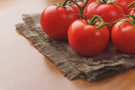 Small red cherry tomatoes wooden table. Summer tray market agriculture farm full of organic tomatoes.