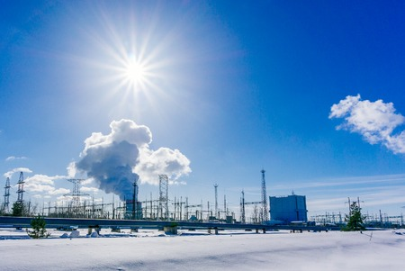 Landscape with view of Nuclear power Plant Clouds of thick smoke on blue sky background at Sunny day. Copy space Stock Photo
