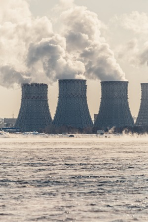 npp: Nuclear or atomic power plant or NPP. Cooling towers with thick smoke and cooling pool. Vertical photo