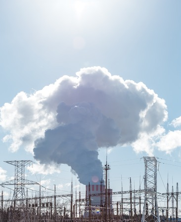 npp: Clouds of thick smoke NPP Nuclear Power Plant in rays of bright sunlight. Vertical photo with copy space for text Stock Photo
