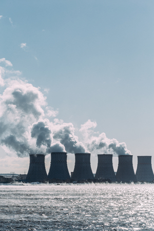 npp: Cooling towers of a Nuclear Power Plant or NPP with thick smoke on blue sky background in sunny day. Copy space for text. Vertical image
