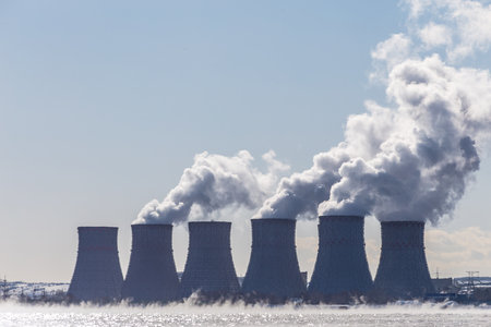 npp: Cooling towers of a Nuclear energy station  or NPP with thick smoke on blue sky background. Copy space for text Stock Photo