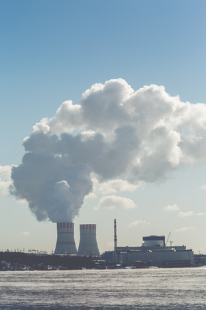 Nuclear power Plant. Clouds of thick smoke on blue sky background. Copy space, vertical image Stock Photo
