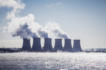 npp: Cooling towers of a Nuclear Power Plant or NPP with thick smoke on blue sky background in sunny day. Copy space for text