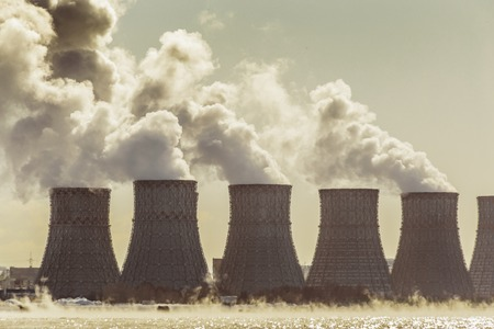 npp: Cooling towers of a Nuclear Power Plant or NPP with thick smoke, toned image. Copy space for text Stock Photo