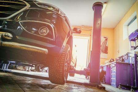 Car in garage of auto repair service shop with special repairing equipment Foto de archivo