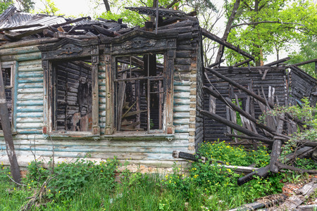Old burned out wooden abandoned mansion, ruined house