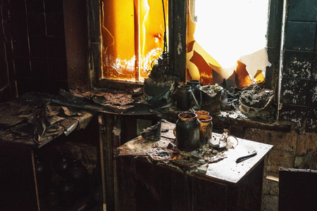 Interior inside the burnt room in burned house, furniture, utensils, charred walls and cracked windows