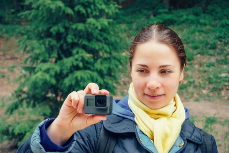 Young woman with action camera at green nature background Stock Photo