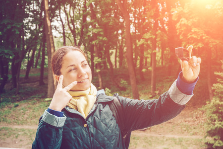 Pretty young woman blogger takes selfie portrait at action camera and shows peace sing by fingers. Blogging, vlog, videoblog and popular mass media concept Stock Photo