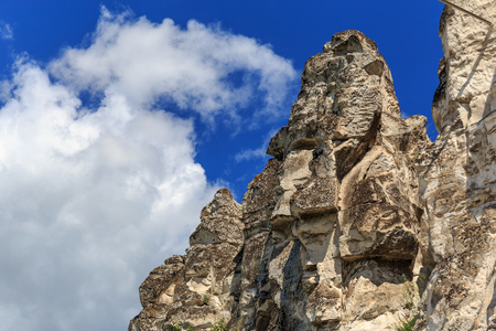 Chalk cliffs or rocks, mountain peak at background blue sky with cloud