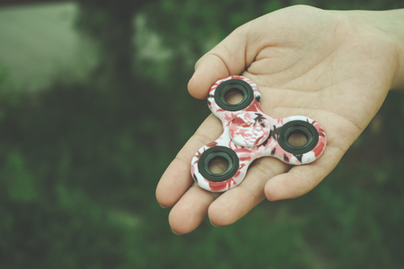 roller: Girl hand holds and shows hand fidget spinner toy, toned image with copy space