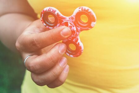 roller: Fidget Spinner toy in girl hand, stress relieving toy, light effect Stock Photo