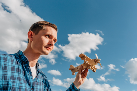 Dreamer, Young man holding in hand wooden toy airplane at blue sky background with copy space. Dreamer and creator concept Stock Photo