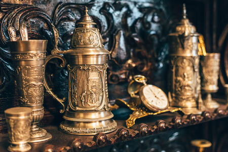 serving utensil: Old antique vintage dishes, large silver mugs, watches, selective focus, toned