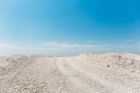 sand quarry: Road in the desert. White sand or chalky rocks against the blue sky. Stock Photo