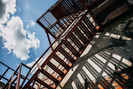 emergency stair: Abstract shot of iron fire staircase outside the building on a Sunny day