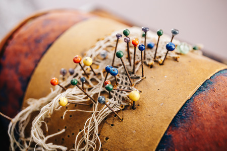 Small needles with coloured tips in a leather pillow. Needlework concept. Selective focus