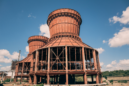 abandoned factory: Old abandoned industrial red cooling towers, toned Stock Photo