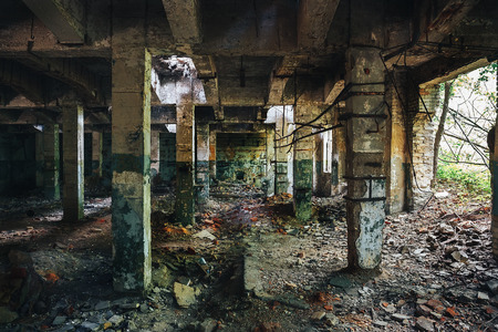 Inside abandoned industrial warehouse with columns and broken wall, toned Stock Photo