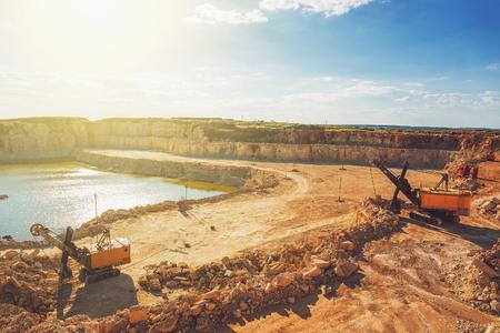 sand quarry: Open cast quarry, machines, excavators in quarry limestone mining in sunlight,