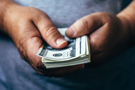 money packs: Mans hands hold a pack of one hundred dollar bills, cash a lot of money concept. Selective focus Stock Photo