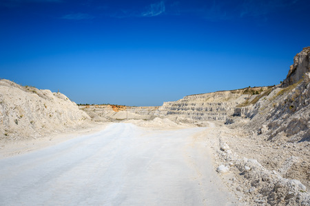 Road to quarry. Limestone mining. White rocks, bright blue sky Stock Photo