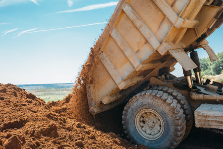 large truck unloads clay and crushed stone, works on a quarry Stock Photo