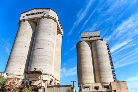 Two concrete towers of agricultural elevator against the blue sky