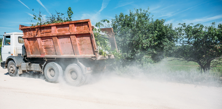 The truck is driving, followed by a cloud of dust, selective focus