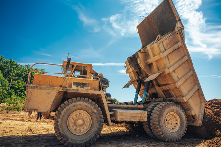 grote industriële gele vrachtwagen lossen proces, de vrachtwagen werkt op een steengroeve mijnbouw