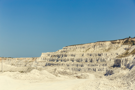 White yellow open cast limestone mining quarry at blue sky background, toned