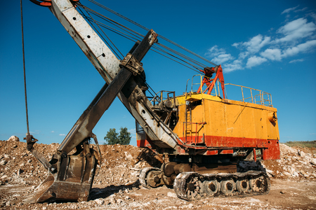 mine site: Quarry orange heavy duty excavator loader at blue sky background