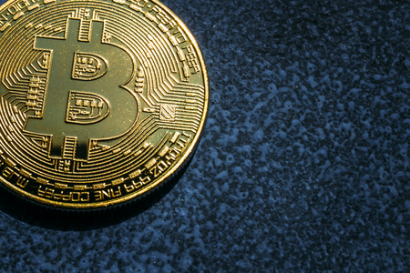 Close-up of Bitcoin golden coin on blue background with copy space, toned Фото со стока