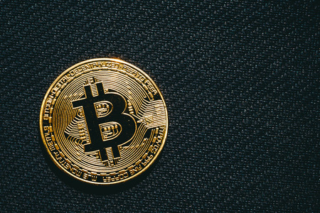 electronic commerce: Bitcoin business concept, golden coin - symbol of Bitcoin on black textured background, copy space