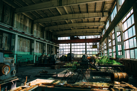 empty warehouse: abandoned factory, empty workplace overgrown with plants