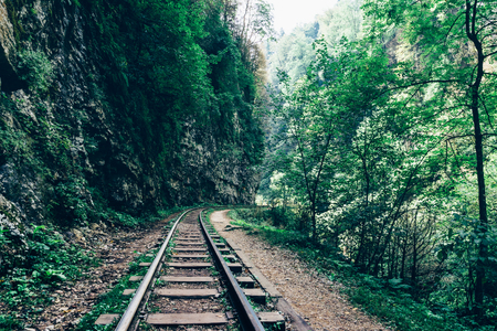 freight train: old abandoned railway among rocks, mountains and forests Stock Photo