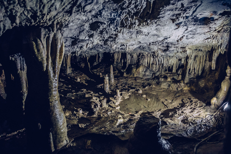 Stalactites and stalagmites inside the underground cave with high humidity, speleology concept Banque d'images