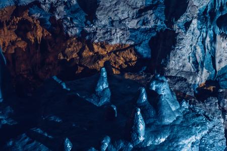 Stalagmites in underground cave in blue light, toned